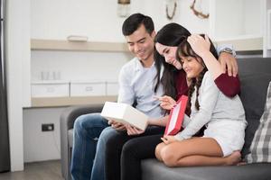 pai e mãe surpreendem a filha com um presente ou um novo brinquedo. pais e filhos são felizes juntos em casa no sofá. família e conceito de felicidade foto