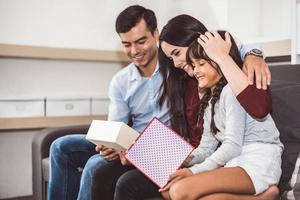 pais de família felizes e a menina olhando para a caixa de presente no Natal e ano novo no sofá na sala de estar. presente de natal para crianças boas surpresas em um lar feliz. conceito de pessoas e estilos de vida foto