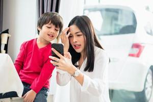 mãe e filho usando e olhando para o smartphone juntos. pessoas e conceito de tecnologia. tema educação e aprendizagem foto