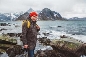 fotógrafo viajante parado nas rochas contra o fundo do mar e da montanha foto