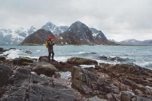fotógrafo viajante tirando foto da natureza de pé nas rochas contra o fundo do mar e das montanhas