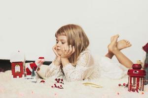 menina deitada no chão, brincando com a decoração de natal foto