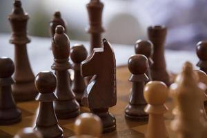 close up de peças de xadrez de madeira em um tabuleiro de xadrez de madeira foto