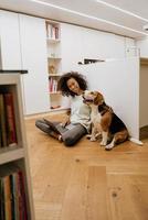 jovem negra usando laptop e acariciando seu cachorro foto