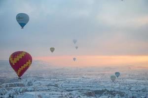 balões de ar quente voando sobre a espetacular Capadócia. bela vista de balões de ar quente flutuando no céu claro do nascer do sol sobre a paisagem montanhosa de Goreme foto