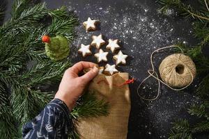 mão de mulher com biscoitos de canela tradicionais. decoração festiva e galhos de árvores de Natal na mesa escura. foto