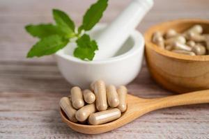 cápsula orgânica de ervas de natureza de medicina alternativa, medicamento com suplementos naturais de folha de ervas para uma vida boa e saudável foto