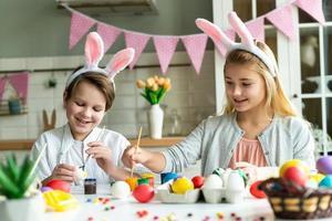 duas crianças felizes em orelhas de coelho pintam ovos de Páscoa na mesa. foto