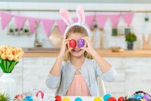 garota sorridente fecha os olhos com ovos de Páscoa na cozinha. foto