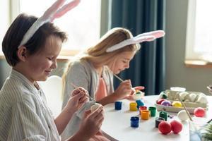 crianças fofas e sorridentes pintam ovos de páscoa com tintas foto