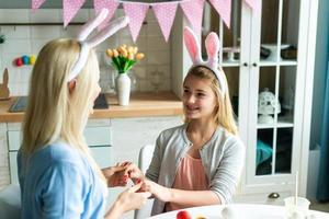 família feliz se preparando para a Páscoa. criança menina bonitinha usando orelhas de coelho no dia de Páscoa. foto