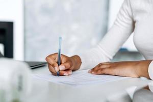 visão de close-up, gentil, mãos femininas assinando documentos em um escritório luminoso foto