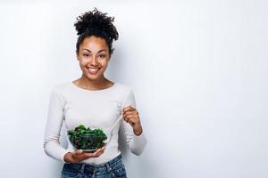 o conceito de alimentação saudável, menina segurando uma tigela de salada, sobre um fundo branco, alimentação saudável foto