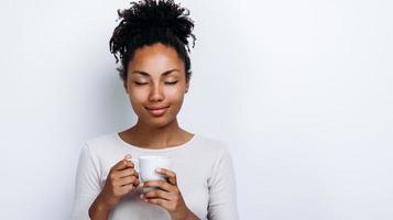 linda garota afro-americana segurando um copo bio, fechando os olhos, apreciando uma bebida em um fundo branco foto