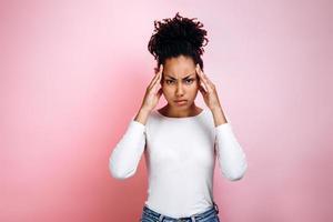 jovem está com dor de cabeça em um fundo rosa foto