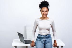 sorridente e atraente mulher de negócios em um fundo de uma área de trabalho em um estúdio branco foto