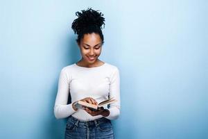 Mulher jovem e atraente com um sorriso lendo um livro interessante sobre um fundo de parede azul foto