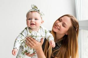 Mãe fofa e sorridente com a filha nos braços, se divertindo foto