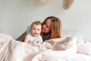 linda jovem mãe e bebê recém-nascido deitado na cama no quarto foto