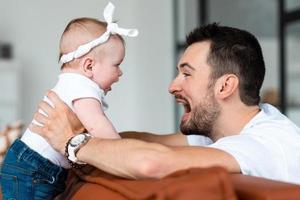 um pai feliz se diverte com sua filhinha foto