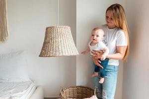 Mulher bonita segurando um bebê recém-nascido nos braços no quarto foto