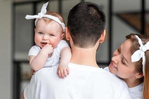 retrovisor, pai segurando a filha nos braços, sorrindo esposa sinceramente feliz. foto