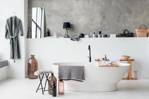 interior moderno do banheiro com iluminação e chuveiro minimalistas, pia e banheira brancas foto