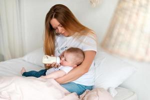 uma jovem e linda mãe dá comida para seu bebê em uma mamadeira foto