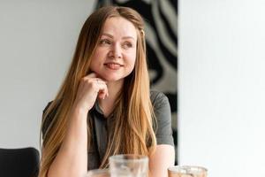uma garota linda e atraente está sentada à mesa, descansando, sonhando com algo foto