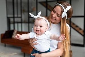 mulher feliz e sorridente segurando uma filha pequena e linda nos braços no apartamento foto