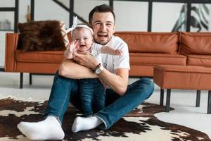 um pai e uma criança estão sentados e o chão está posando lindamente para a câmera foto