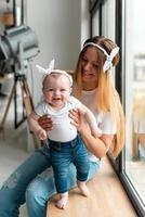 linda menina nos braços de uma jovem mãe. foto