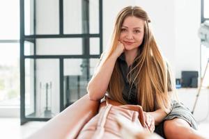mulher atraente, bonita e jovem, olhando diretamente para a câmera. sentado no sofá foto