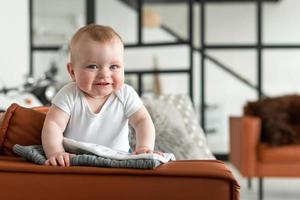 linda, fofa, garotinha em pé no sofá sinceramente se alegra foto
