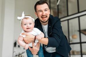 pai alegre com sua filha pequena se divertir. mima seu filho foto