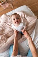 lindo, lindo bebezinho brincando com a mãe, olhando para ela. conceito de cuidado, amor, proteção e carinho. foto