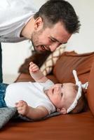 linda garota deitada sobre ela com amor, olhando para seu pai atraente foto