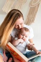 uma jovem lê um livro para sua filha pequena, fofa e linda foto
