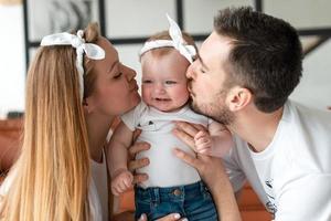 uma mãe e um pai beijando seu bebê foto