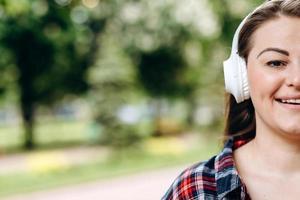 a foto mostra metade do rosto de uma mulher bonita e sorridente usando fones de ouvido brancos