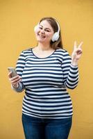 linda mulher sorridente com fones de ouvido sem fio brancos mostra gesto de paz em fundo laranja foto