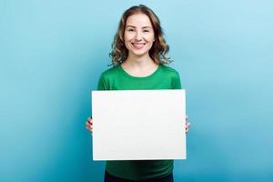 menina loira vestindo um suéter verde segurando um espaço de cópia de quadro branco contra um fundo azul foto