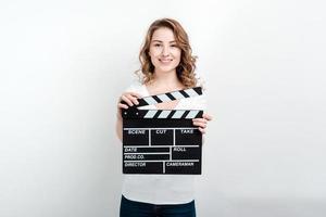 mulher segurando uma claquete de produção de filme olhando para a câmera foto