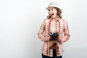 foto do turista do fotógrafo jovem animado em pé sobre um fundo branco, segurando a câmera.