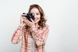 retrato de uma garota feliz usando uma câmera retro sobre o fundo branco do estúdio foto