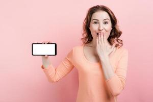 garota feliz segurando um smarphone na mão e mostrando a tela de maquete em branco vazia foto