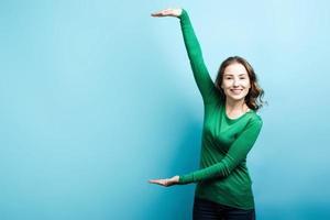 linda garota loira vestindo um suéter verde, mostrando um espaço de cópia com as mãos contra um fundo azul foto