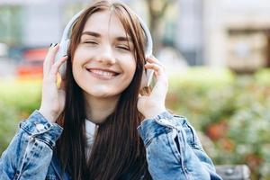 linda garota de olhos fechados em fones de ouvido, sinceramente sorrindo, curtindo sua música favorita foto