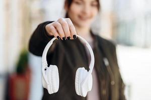 em um fundo desfocado, a garota é claramente visível como uma mão segurando fones de ouvido foto