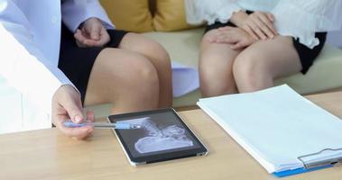o médico está explicando sobre os resultados das radiografias do cérebro a uma paciente em seu consultório em hospitais foto
